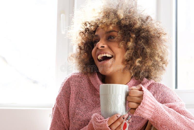 Attraktive junge Afroamerikanerfrau, die das Halten der Tasse Tee hält lizenzfreie stockbilder