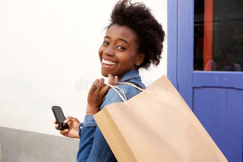 Attraktive junge Afroamerikanerfrau, die mit Telefon und Einkaufstasche lächelt lizenzfreie stockbilder