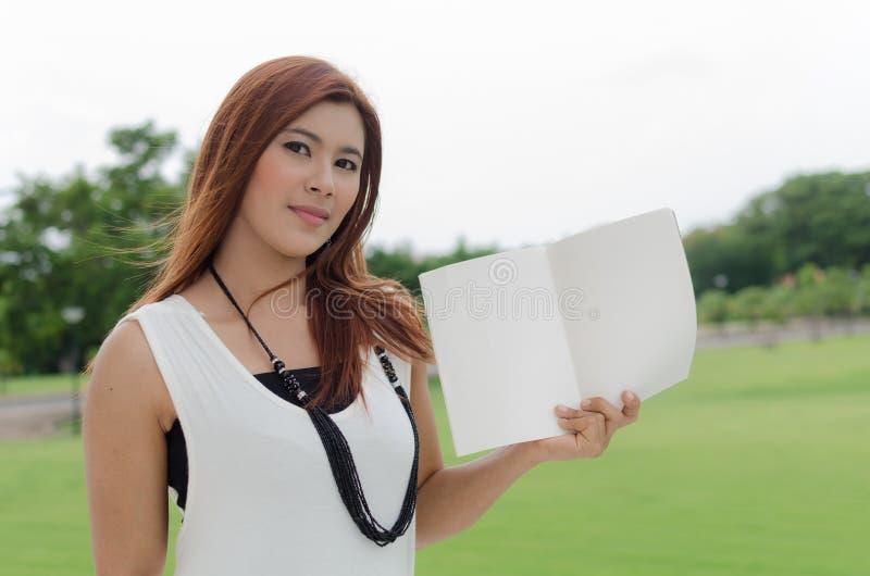 Attraktive junge Asiatin, die ein offenes Buch hält stockfoto