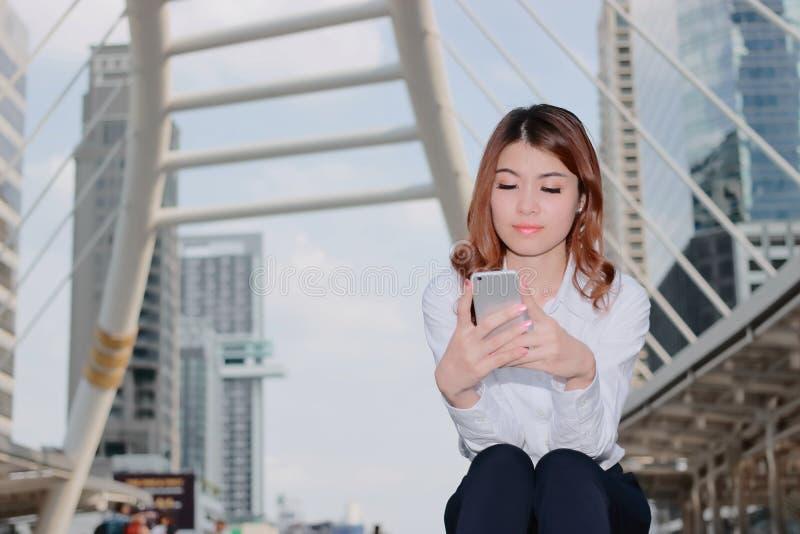 Attraktive junge Asiatin im weißen Hemd, das intelligentes Mobiltelefon in ihren Händen städtischem errichtendem Hintergrund betr stockbilder