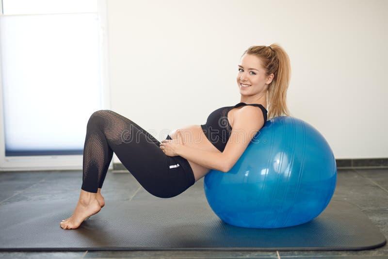 Attraktive junge blonde schwangere Frau, die mit einem pilates Ball ausarbeitet stockbilder