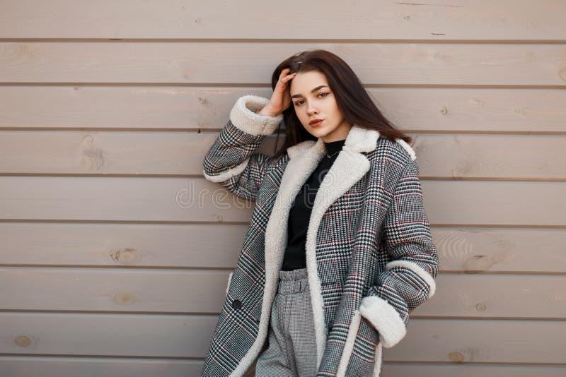 Attraktive junge brunette Frau in einem modischen T-Shirt in einer karierten Jacke der Weinlese in den grauen stilvollen Hosen st stockbild