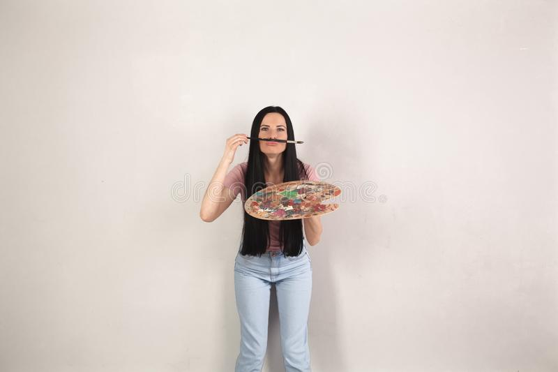 Attraktive junge brunette Frau mit dem langen Haar steht den grauen Hintergrund mit der Farbenpalette bereit, die den Spaß hat, d stockfoto