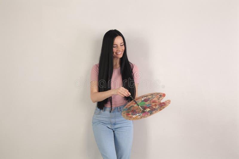 Attraktive junge brunette Frau mit dem langen Haar steht den grauen Hintergrund mischt verschiedene Farben von Farben auf Palette stockfotografie