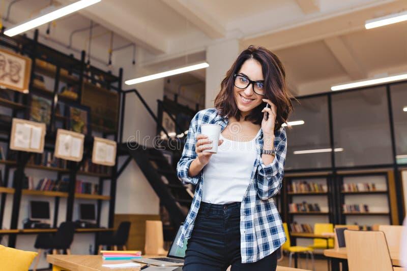 Attraktive junge brunette Frau mit Kaffee sprechend am Telefon und zur Kamera in der Bibliothek lächelnd Kaffee-Bruch, Universitä stockfotografie