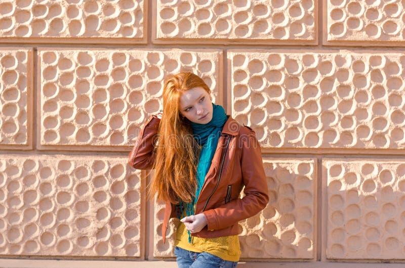 Attraktive junge Dame, die vor dem rosa brickwall aufwirft lizenzfreies stockfoto