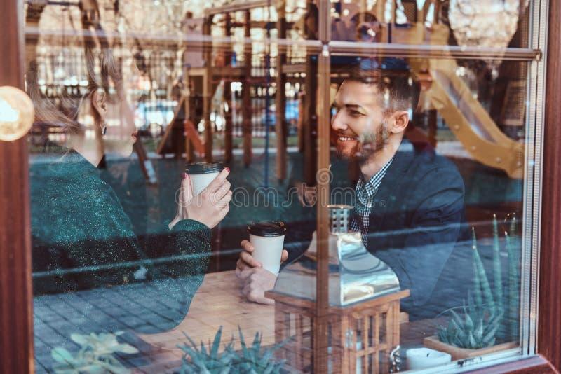 Attraktive junge einander betrachtende und beim Sitzen sprechende Paare im Restaurant hinter dem Fenster stockfotos