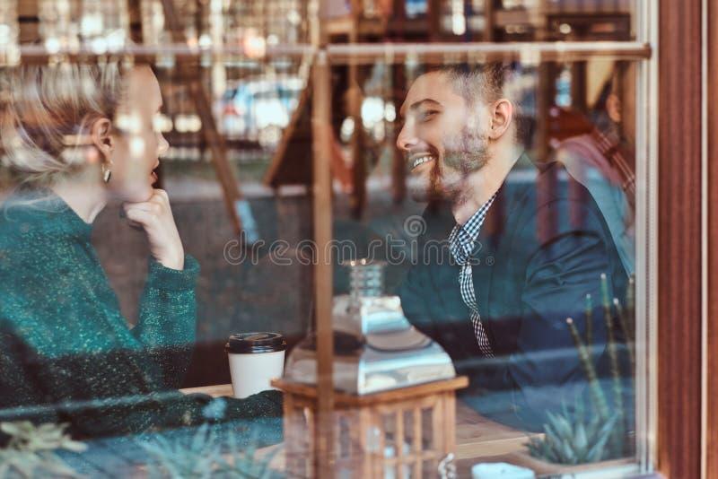 Attraktive junge einander betrachtende und beim Sitzen sprechende Paare im Restaurant hinter dem Fenster lizenzfreies stockbild