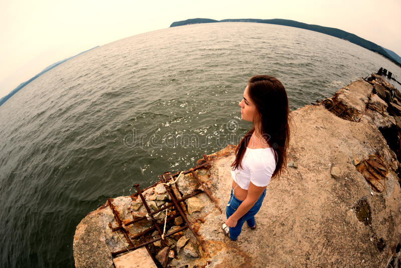Attraktive junge Frau auf dem alten Pier das Meer stockbild