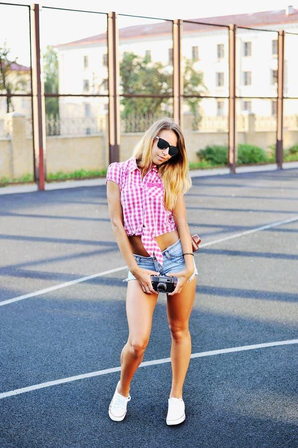 Attraktive junge Frau bei der Sonnenbrilleaufstellung im Freien - volles lengt stockfoto