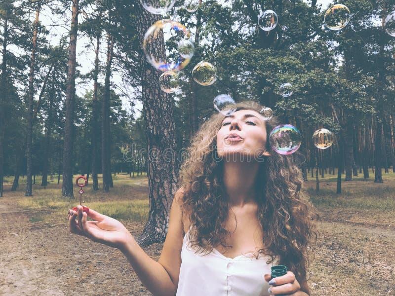 Attraktive junge Frau brennt Seifenblasen im Wald durch stockbilder