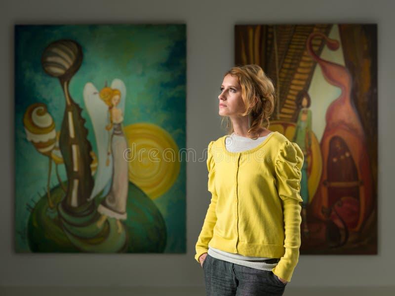 Attraktive junge Frau an der Kunstausstellung stockfotografie
