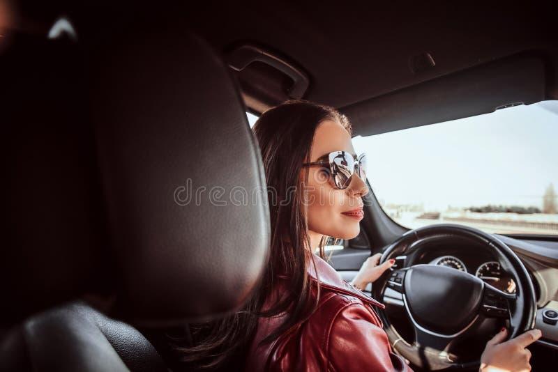 Attraktive junge Frau in der roten Jacke und in der Sonnenbrille, wenn ihr Auto gefahren wird stockfotos