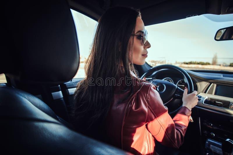 Attraktive junge Frau in der roten Jacke und in der Sonnenbrille, wenn ihr Auto gefahren wird stockfoto
