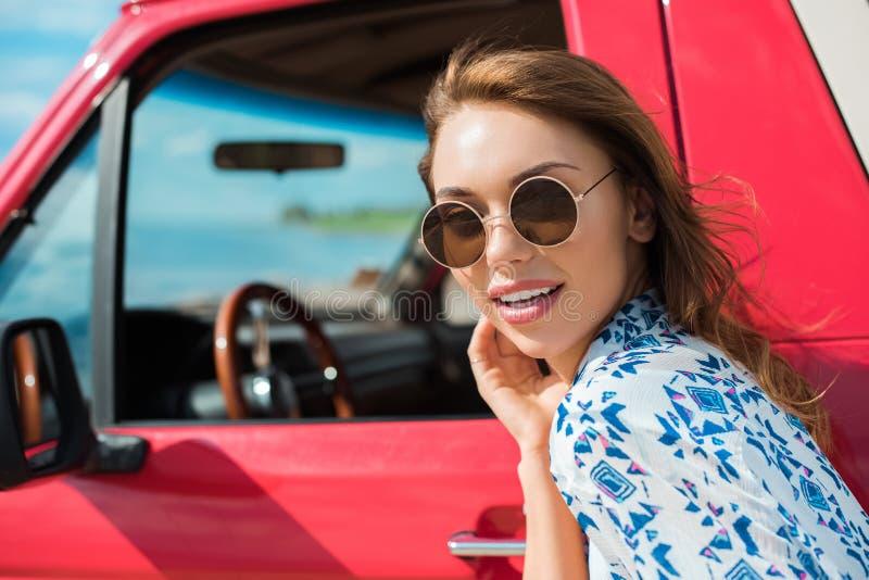 attraktive junge Frau in der Sonnenbrille nahe rotem Auto stockfoto