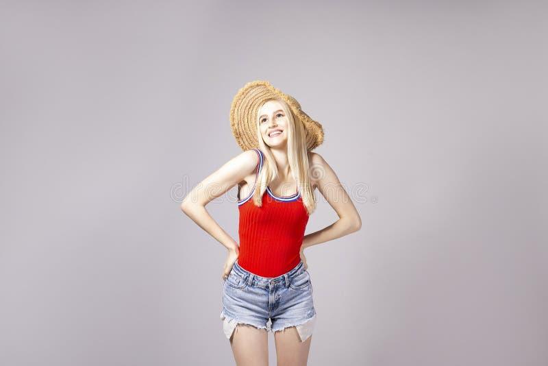 Attraktive junge Frau, die über grauem Hintergrund aufwirft stockfoto