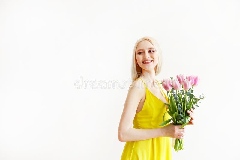 Attraktive junge Frau, die ?ber grauem Hintergrund mit Blumen aufwirft lizenzfreies stockfoto