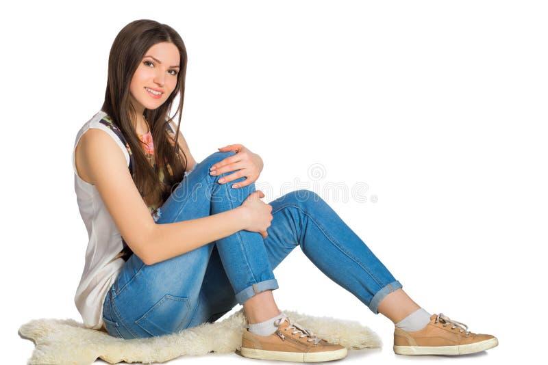 Attraktive junge Frau, die auf dem Boden lokalisiert sitzt stockfoto