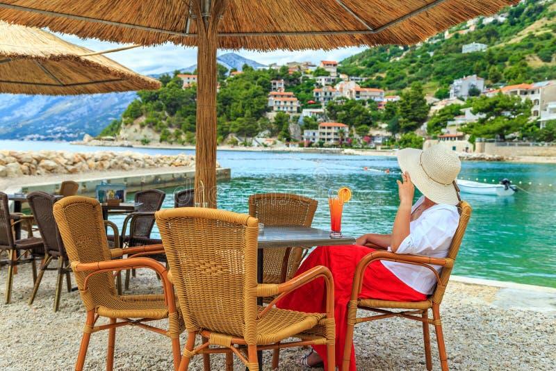 Attraktive junge Frau, die auf einem tropischen Strand sich entspannt lizenzfreie stockbilder