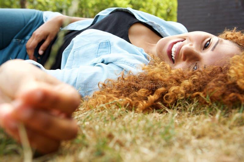 Attraktive junge Frau, die auf Grasaußenseite liegt lizenzfreie stockfotos