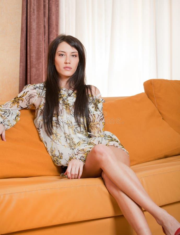 Attraktive junge Frau, die auf Sofa sitzt lizenzfreies stockbild