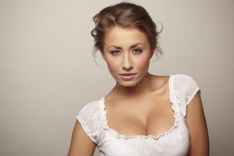Attraktive junge Frau, die auf weißem Hintergrund sich entspannt lizenzfreies stockbild