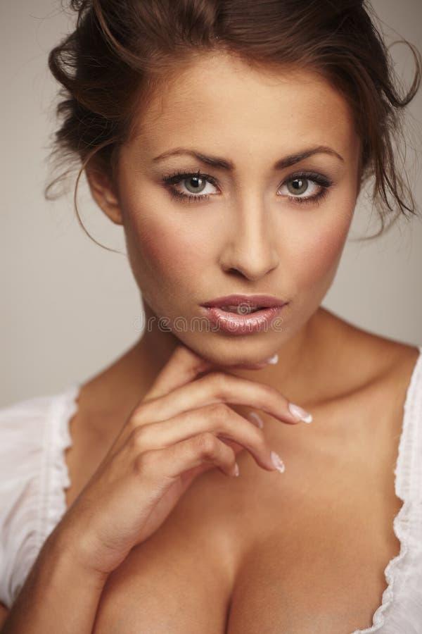 Attraktive junge Frau, die auf weißem Hintergrund sich entspannt lizenzfreie stockbilder