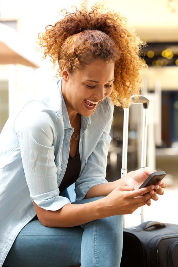 Attraktive junge Frau, die draußen über Textnachricht lacht lizenzfreie stockfotografie