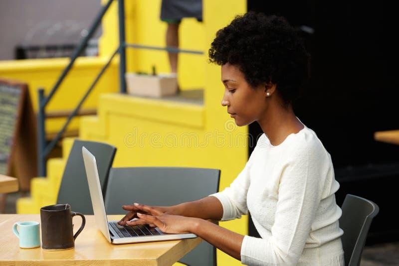 Attraktive junge Frau, die draußen Laptop verwendet stockbild