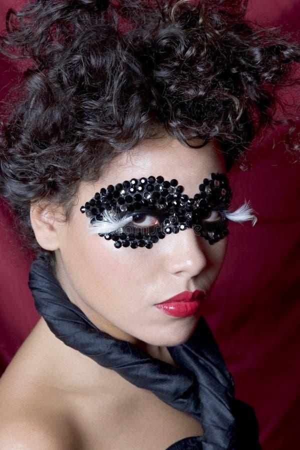 Attraktive junge Frau, die eine schwarze Edelsteinmaske trägt lizenzfreies stockbild