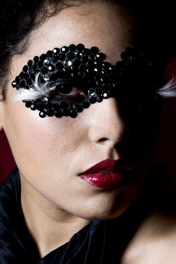 Attraktive junge Frau, die eine schwarze Edelsteinmaske trägt stockfoto