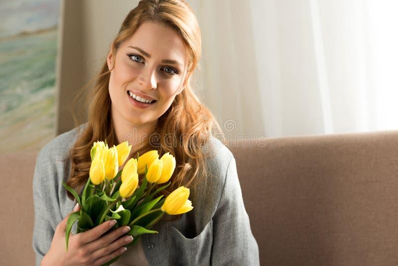 attraktive junge Frau, die gelbe Tulpen und das Lächeln hält lizenzfreie stockbilder