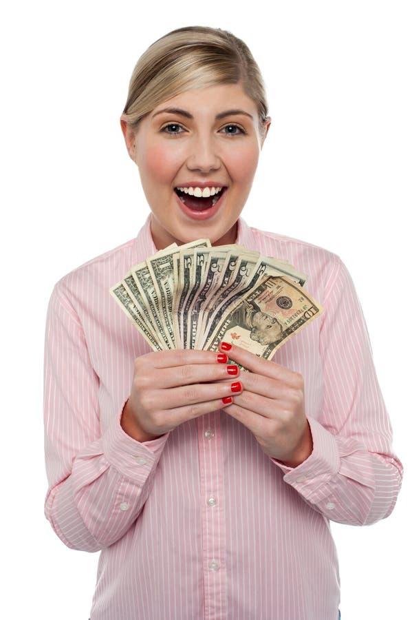 Attraktive junge Frau, die Geld anhält stockbilder