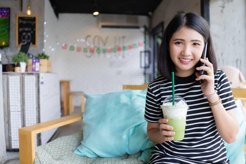 Attraktive junge Frau, die am Handy an der Kaffeestube trinkt grünen Tee beim Sitzen auf dem Sofa mit glücklicher Gesichtsbehandl stockbilder