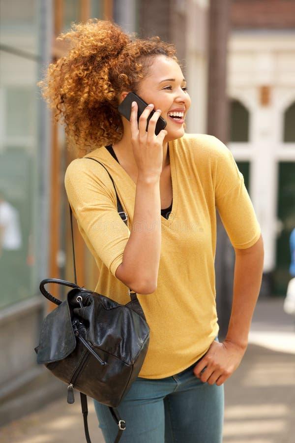 Attraktive junge Frau, die am Handy in der Stadt geht und spricht stockfoto