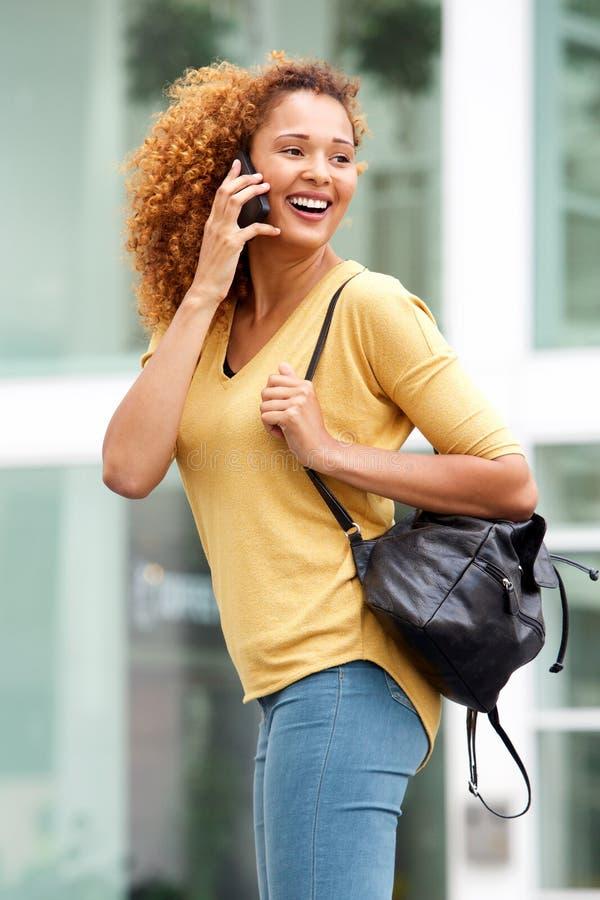 Attraktive junge Frau, die am Handy in der Stadt spricht lizenzfreie stockbilder