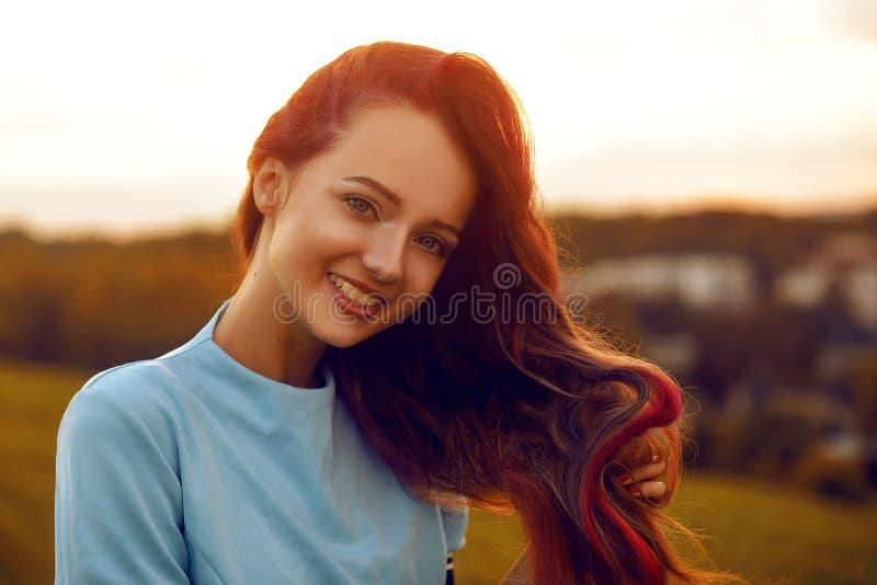Attraktive junge Frau, die ihre Zeit draußen im Sonnenuntergangpark genießt Vorbildliches Mädchen mit der ausgezeichneten langen  stockfotografie