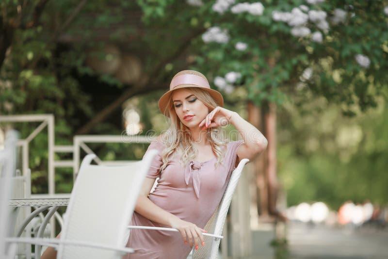 Attraktive junge Frau, die ihre Zeit drau?en im Park mit Sonnenuntergang im Hintergrund genie?t stockbild