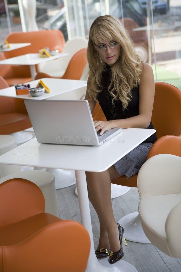 Attraktive junge Frau, die mit einem Laptop arbeitet lizenzfreies stockfoto