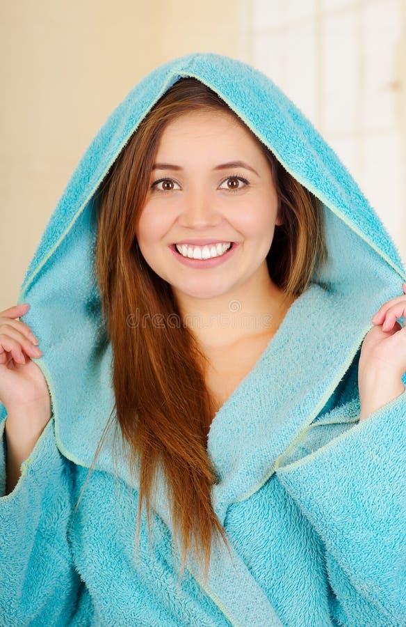 Attraktive junge Frau, die mit Kapuze blauen Bademantel trägt lizenzfreies stockfoto