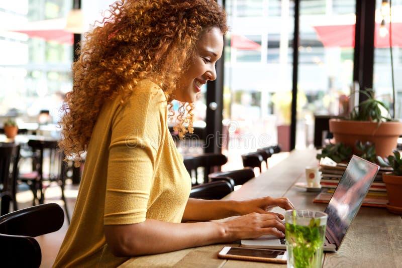 Attraktive junge Frau, die mit Laptop am Café arbeitet lizenzfreies stockbild