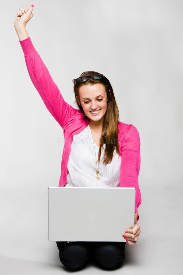 Attraktive junge Frau, die mit Laptop feiert stockfoto