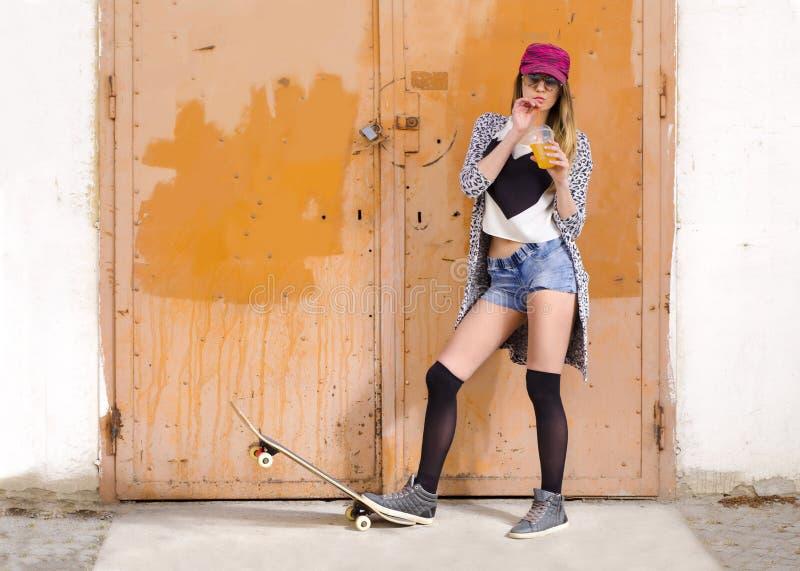 Attraktive junge Frau, die mit Skateboard und trinkendem Saft aufwirft lizenzfreie stockfotografie