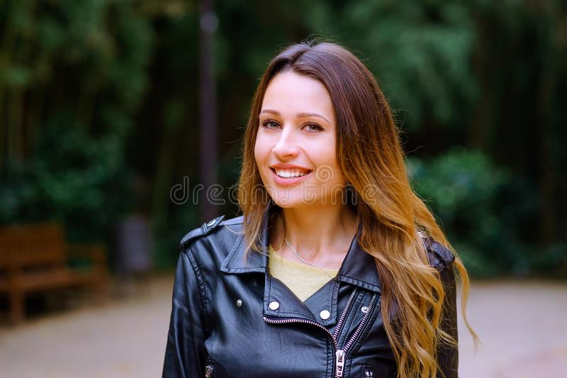 Attraktive junge Frau, die reizend Kamera lächelt und betrachtet lizenzfreie stockbilder