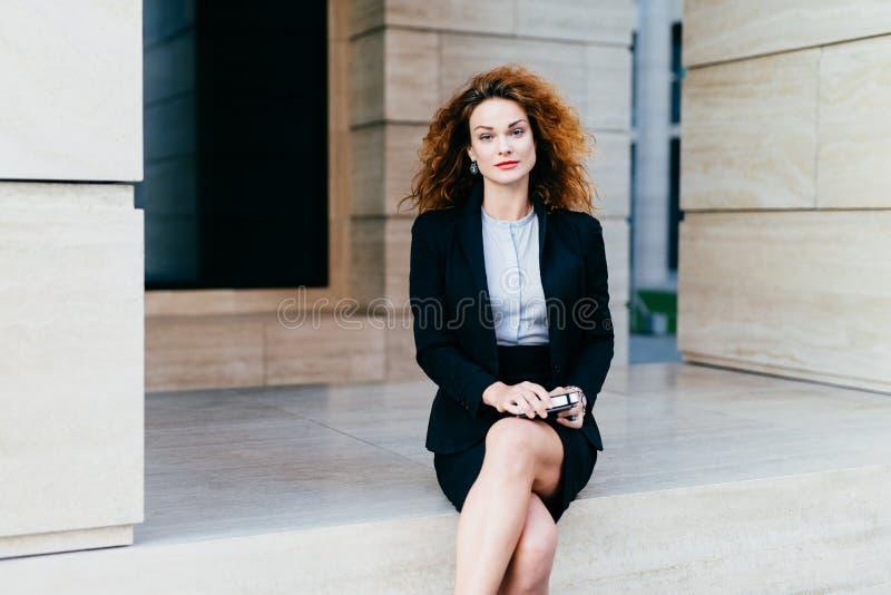 Attraktive junge Frau, die schwarzen Gesellschaftsanzug, sitzende gekreuzte Beine mit WarteTeilhaber des elektronischen Geräts na lizenzfreie stockfotos