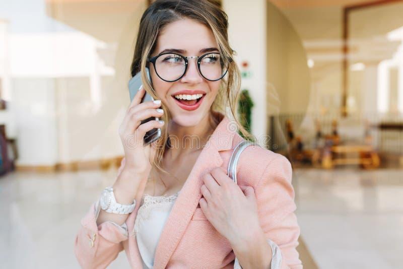 Attraktive junge Frau, die telefonisch, schauend mit der Seite lächelt und spricht und stehen in der Halle Sie hat weiße kurze Ma lizenzfreie stockbilder