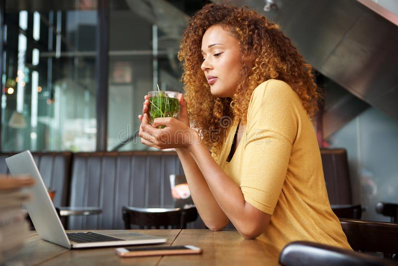 Attraktive junge Frau, die an trinkendem Tee des Cafés sitzt lizenzfreie stockfotos