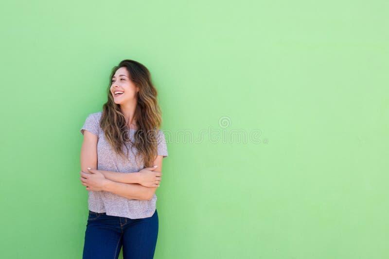 Attraktive junge Frau, die weg auf grünem Hintergrund lächelt und schaut lizenzfreies stockbild