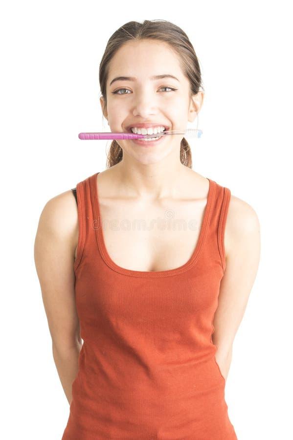 Attraktive junge Frau, die Zahnbürste anhält stockfoto