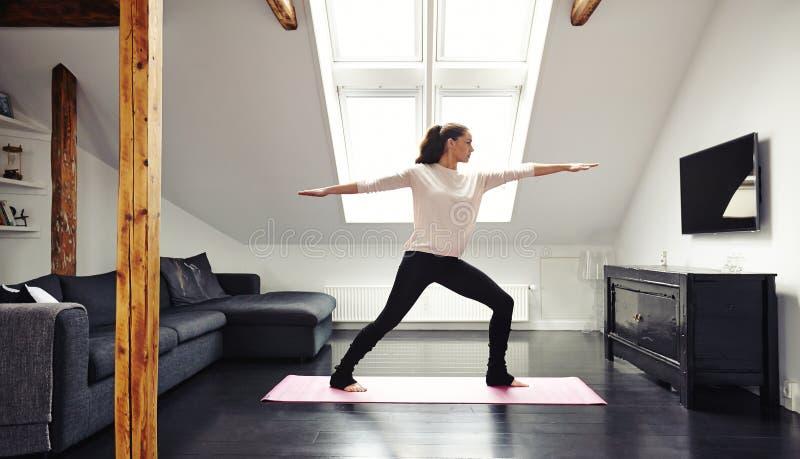 Attraktive junge Frau, die zu Hause Yoga tut stockfoto